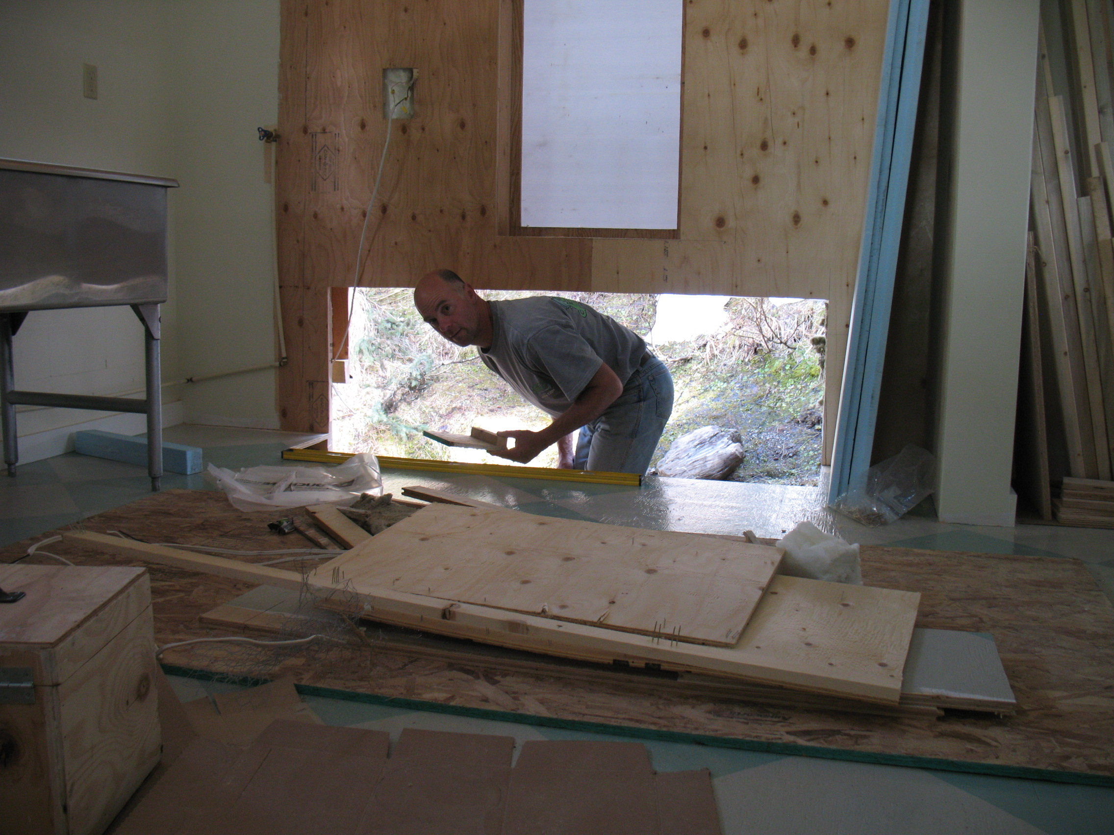 Cutting into the bakery floor and wall in preparation for building the base of the oven.