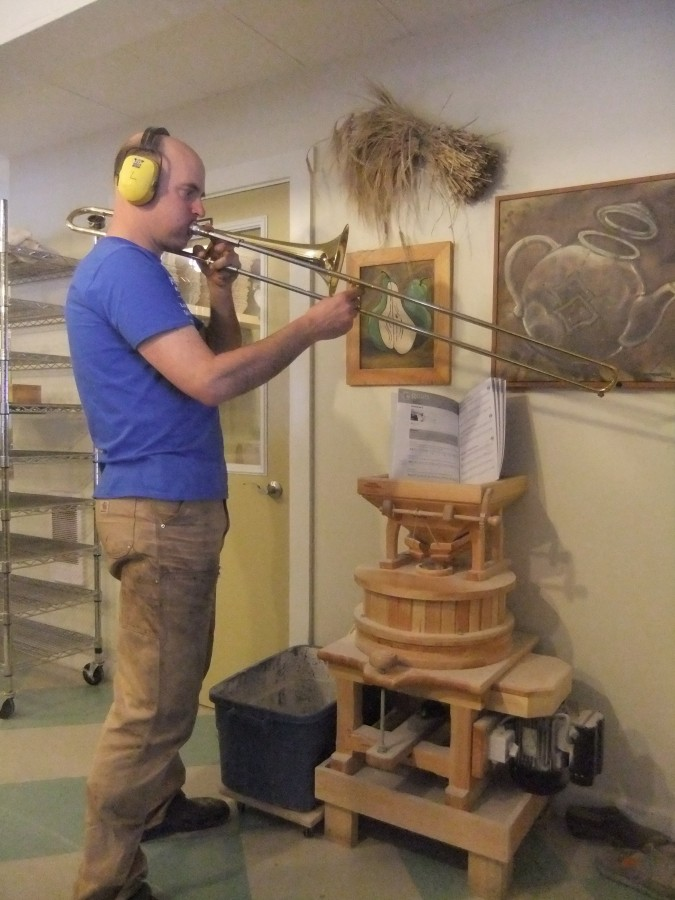 And who says men can't multi-task? It's a regular Monday for Tim: milling grain, tending the fire, AND playing the trombone. What's with the ear protection, Tim?