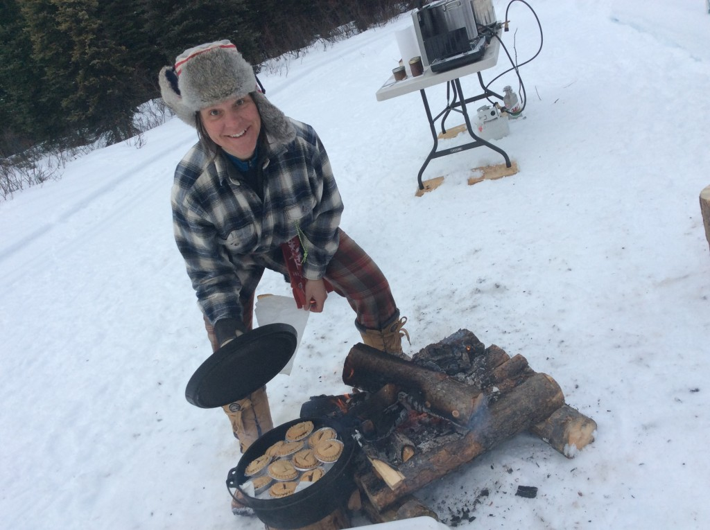 A Bread Peddler moonlighting as a Quebécoise - showing off mini tourtières heating by the fire.